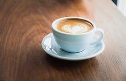 Feche acima do copo de café quente do cappuccino com arte do latte da forma do coração sobre imagem de stock