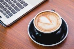 Feche acima do copo de café quente do cappuccino com ne da arte do latte da forma do coração foto de stock royalty free