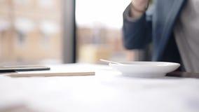 Feche acima do copo de café tomado da tabela pela mão do homem de negócios vídeos de arquivo