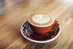 Feche acima do copo de café vermelho do cappuccino quente com latte AR da forma do coração fotos de stock royalty free