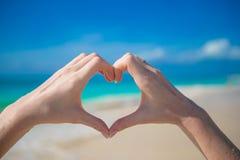 Feche acima do coração feito pelo fundo das mãos da fêmea o oceano de turquesa Imagens de Stock Royalty Free