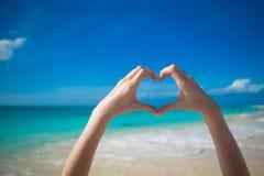 Feche acima do coração feito pelo fundo das mãos da fêmea o oceano de turquesa Fotos de Stock