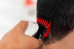 Feche acima do corte de máquina vermelho um cabelo do homem, cabelo curto Fotos de Stock