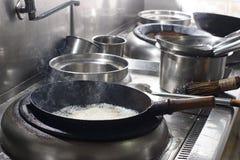 Feche acima do cozinheiro chefe de trabalho que prepara o alimento chinês Foto de Stock