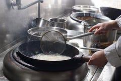 Feche acima do cozinheiro chefe de trabalho que prepara o alimento chinês Imagens de Stock