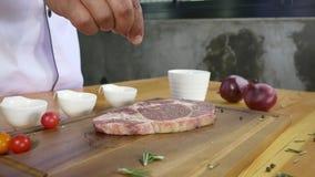 Feche acima do cozinheiro chefe gourmet ou do cozinheiro que temperam o pedaço fresco da parte do supermercado fino de carne com  filme