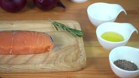 Feche acima do cozinheiro chefe gourmet ou do cozinheiro que temperam o pedaço fresco da parte do supermercado fino dos peixes sa filme