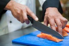 Feche acima do cozinheiro chefe que corta salmões com faca afiada imagem de stock royalty free