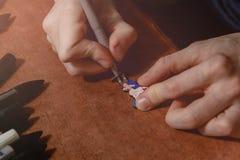Feche acima do crachá da pintura do ofício da mão do homem da madeira pelo marcador permanente no local de trabalho Conceito feit imagens de stock