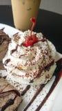 Feche acima do creme de chicoteamento coberto com chocolate e cereja Foto de Stock