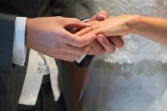 Feche acima do dedo dos €™s de Putting Wedding Ring On Brideâ do noivo foto de stock royalty free