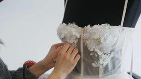 Feche acima do desenhador de moda para noivas em seus pinos que do estúdio as agulhas atam e flores ao vestido de casamento A cos vídeos de arquivo