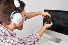 Feche acima do detalhe de gamer masculino farpado novo que joga jogos no computador pessoal com o controlador nos fones de ouvido Imagens de Stock Royalty Free