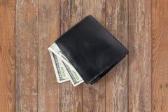 Feche acima do dinheiro do dólar na carteira preta na tabela Fotografia de Stock Royalty Free