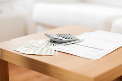 Feche acima do dinheiro e da calculadora na tabela em casa Fotos de Stock