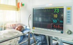 Feche acima do dispositivo digital para medir o monitor da pressão sanguínea com sono paciente idoso na cama no hospital Fotografia de Stock