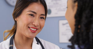 Feche acima do doutor asiático feliz que olha o paciente Foto de Stock