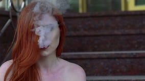 Feche acima do e-cigarro de fumo da senhora apaixonado, sentando-se nas escadas lentamente vídeos de arquivo