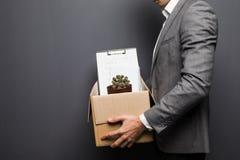 Feche acima do empregado ateado fogo do homem que esconde atrás da caixa com artigos pessoais no fundo cinzento Foto de Stock Royalty Free