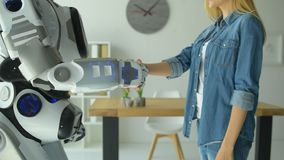Feche acima do empregado do sexo feminino e do robô que agitam as mãos no escritório video estoque