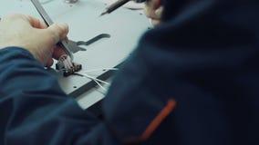 Feche acima do engenheiro eletrónico que trabalha com uma placa de circuito video estoque