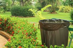 Feche acima do escaninho reciclado e do saco de lixo pl?stico preto no parque p?blico imagem de stock