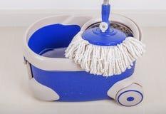 Feche acima do espanador e da cubeta azul para o assoalho de limpeza Imagem de Stock