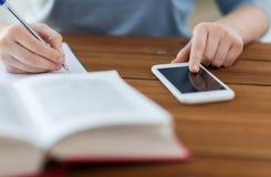 Feche acima do estudante com smartphone e caderno foto de stock