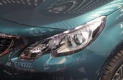 Feche acima do farol do carro verde metálico Fotografia de Stock Royalty Free