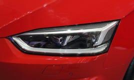 Feche acima do farol direito do carro desportivo luxuoso vermelho Imagem de Stock