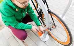 Feche acima do fechamento da bicicleta da asseguração do homem no estacionamento fotos de stock royalty free