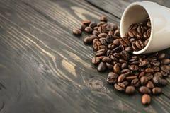 Feche acima do feijão de café e da parte superior do copo na madeira Fotografia de Stock Royalty Free