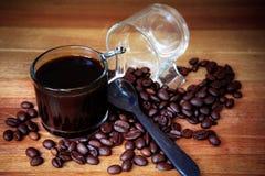 Feche acima do feijão de café e disparado do café preto na tabela de madeira imagem de stock royalty free