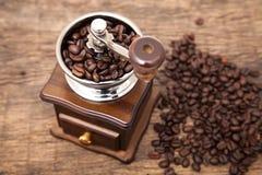 Feche acima do feijão de café fresco no moedor do feijão de café Fotografia de Stock