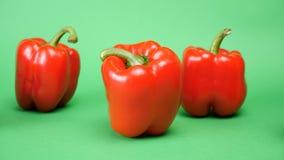 Feche acima do foco da zorra que segue em cinco pimentas vermelhas doces no fundo verde filme