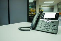 Feche acima do foco macio em dispositivos do telefone do IP com espaço na mesa de escritório imagem de stock