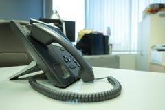 Feche acima do foco macio em dispositivos do telefone do IP na mesa de escritório foto de stock