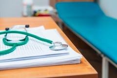 Feche acima do foco no título do estetoscópio do terapeuta nos formulários médicos na tabela de madeira com o sofá médico no fund imagem de stock royalty free