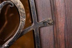 Feche acima do fragmento do teste padrão do metal na porta de madeira Fotos de Stock Royalty Free