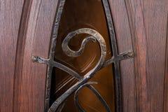 Feche acima do fragmento do teste padrão do metal na porta de madeira Imagens de Stock Royalty Free