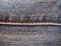 Feche acima do fundo abstrato da textura das calças de brim da emenda Fotos de Stock