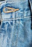 Feche acima do furo de botão em calças de brim Imagem de Stock