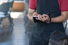 Feche acima do garçom masculino asiático escrevem ordens dos costumers no café no fundo imagens de stock royalty free