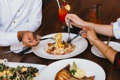 Feche acima do grupo de mãos dos amigos com uma forquilha que tem o divertimento que come e que tem o jantar italiano junto fotografia de stock royalty free