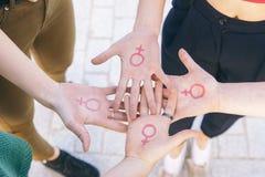 Feche acima do grupo pequeno de mulheres com o símbolo do wri do feminismo imagem de stock royalty free