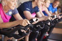 Feche acima do grupo que toma a classe da rotação no Gym imagens de stock