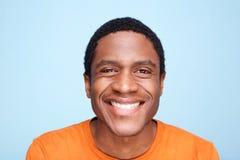 Feche acima do homem afro-americano que sorri contra o fundo azul imagem de stock