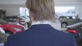 Feche acima do homem alto no terno que anda entre fileiras de carros novos na exposição automóvel que olha em torno de escolher u filme
