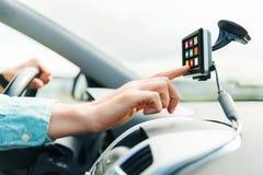Feche acima do homem com ícones no dispositivo que conduz o carro Foto de Stock Royalty Free