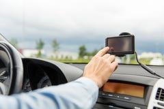 Feche acima do homem com o navegador dos gps que conduz o carro Fotografia de Stock Royalty Free